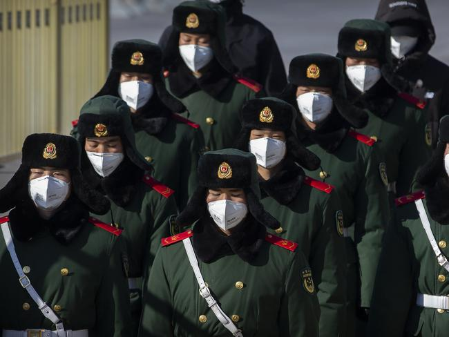 Paramilitary policemen wear face masks as they march in formation into a pedestrian underpass next to Tiananmen Square in Beijing