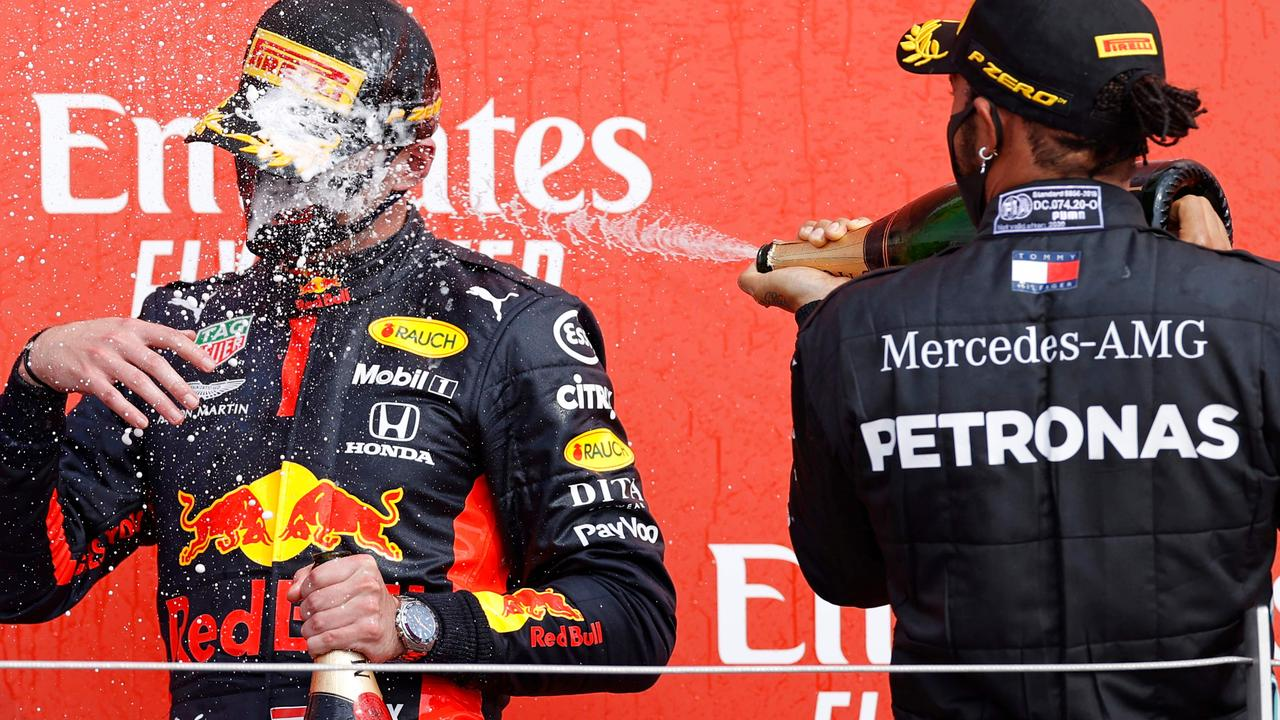 Mercedes driver Lewis Hamilton sprays champagne at Red Bull's Dutch driver Max Verstappen after he won the race during the F1 70th Anniversary Grand Prix.