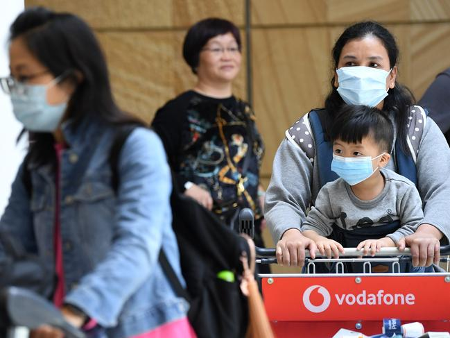 Passengers wearing protective masks arrive at Sydney International Airport in Sydney. Australia is working to keep out the deadly coronavirus, as a flight from the city at the centre of the outbreak arrives in Sydney. Picture: AAP