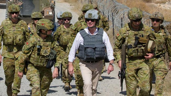Defence Minister Christopher Pyne, centre, is escorted to Camp Qargha by Australian Defence Force personnel.