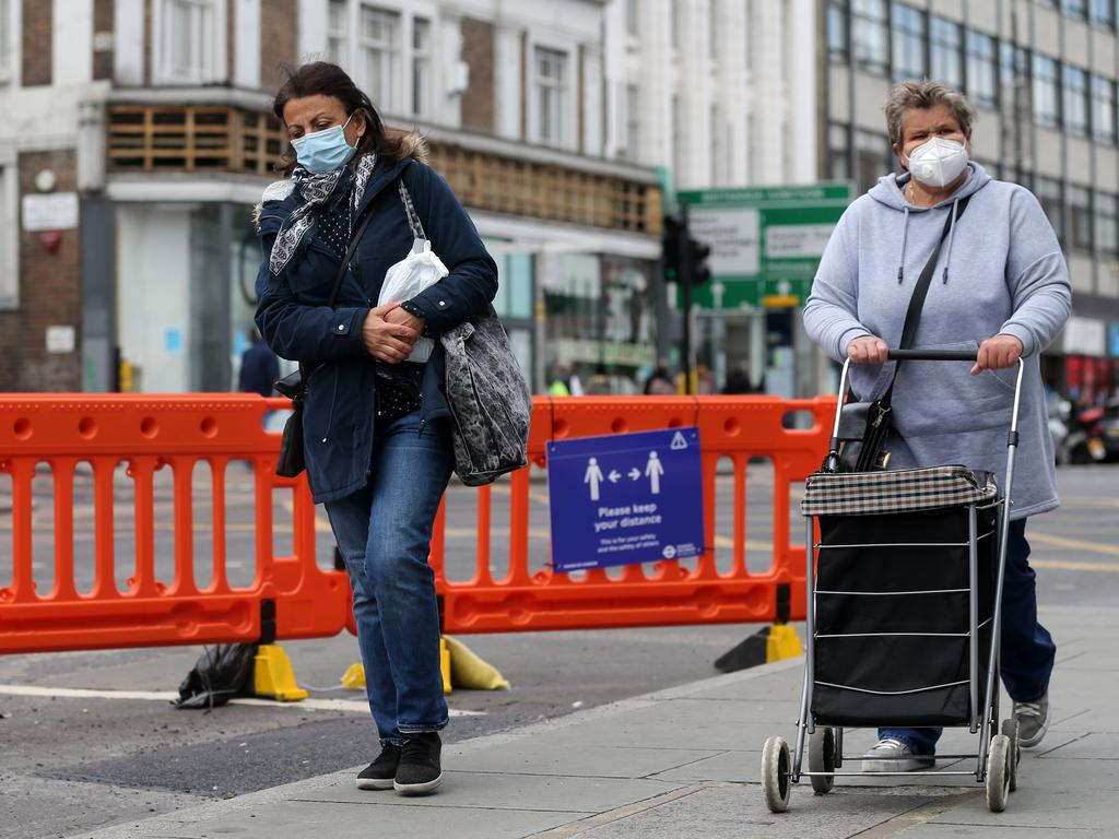 Women wear face masks as they walk down Camden High Street in central London. Picture: AFP