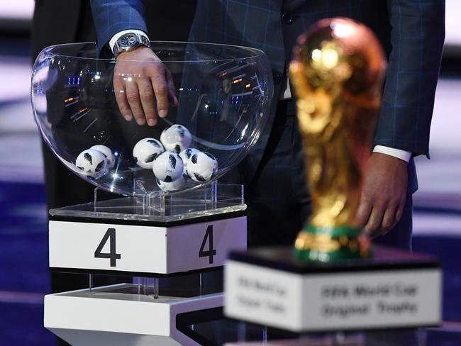 A draw assistant picks up a ball next to the official FIFA World Cup trophy