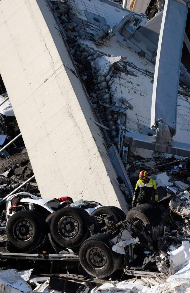 Rescuers inspect the rubble and wreckages by the Morandi motorway bridge after a section collapsed earlier in Genoa. Picture: AFP
