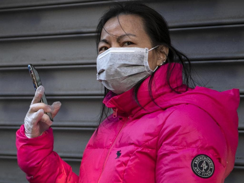A woman wears surgical gloves and a face mask as she speaks on her smart phone in Chinatown in New York.