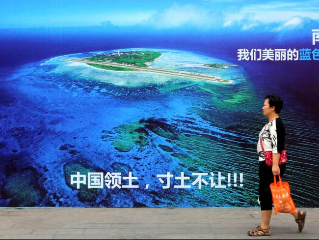 A woman walks past a billboard featuring an image of an island in South China Sea on display with Chinese words that read: 'South China Sea, our beautiful motherland, we won't let go an inch'. Picture: AP