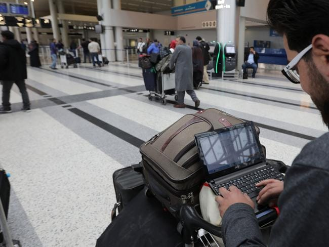A Syrian passenger travelling to the United States through Jordan checks his laptop before entering the departure lounge at Beirut's international airport. Picture: AFP/Anwar Amro