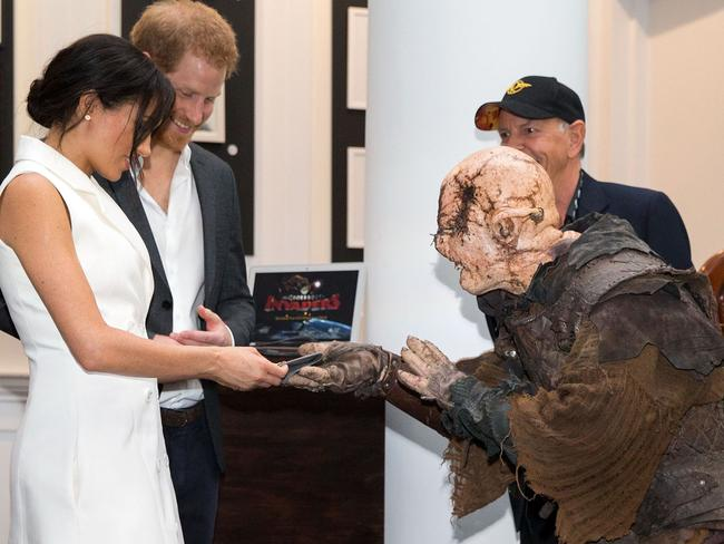 Britain's Prince Harry (2nd L) and his wife Meghan, Duchess of Sussex (L) are presented with a gift from a performer dressed as an Orc during a visit to Courtney Creative in Wellington. Picture: AFP