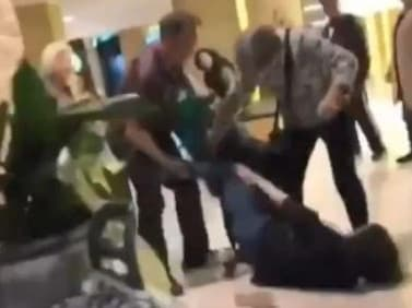 A shopper lies on the ground kicking others during a brawl over baby formula.