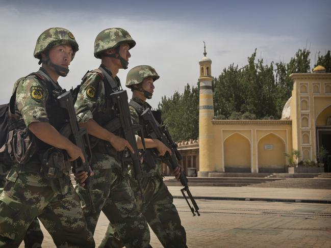 Chinese soldiers march in front of the Id Kah Mosque, China's largest, in Kashgar, China. Picture: Getty