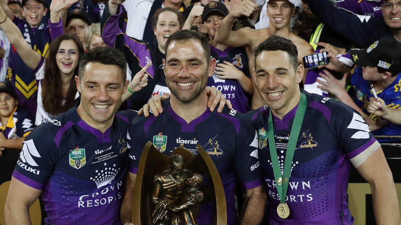 Melbourne Storm captain Cameron Smith raises the Provan-Summons Trophy with Cooper Cronk (L) and Billy Slater (R)