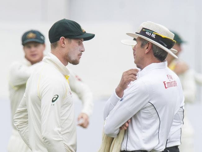Umpires Nigel Llong and Richard Illingworth confront Australia's Cameron Bancroft.