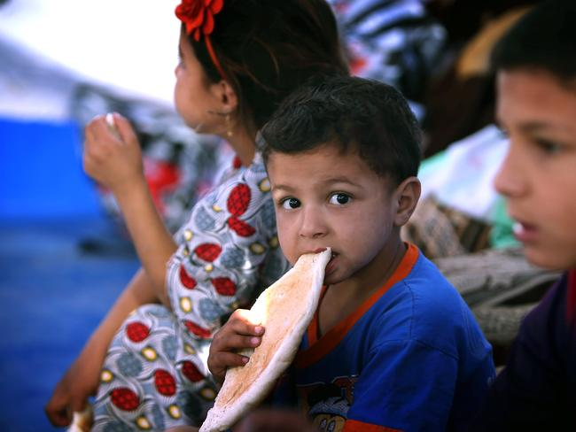 Refugees ... Children eat at a temporary camp set up to shelter Iraqis fleeing violence in Iraq's northern Nineveh province in Aski kalak, 40 kilometres West of Arbil, in the autonomous Kurdistan region.