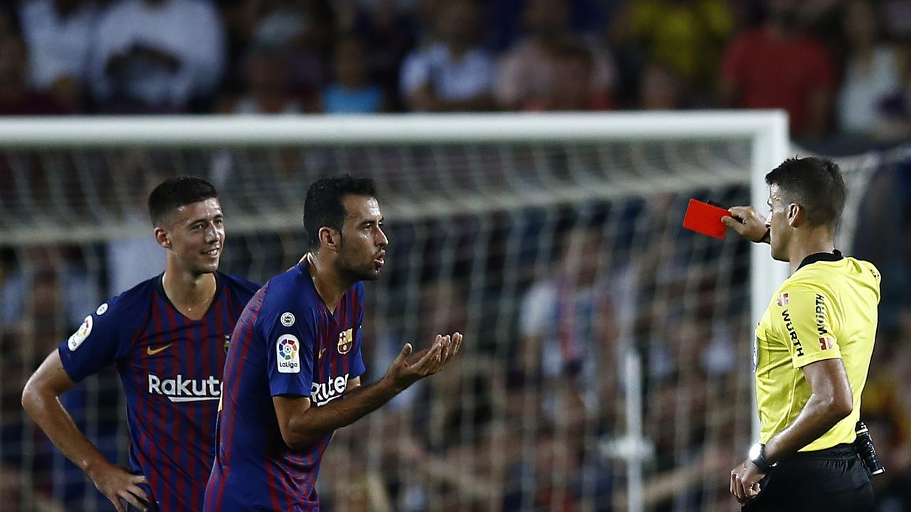 Referee Gil Manzano, right, shows a red card to FC Barcelona Clement Lenglet