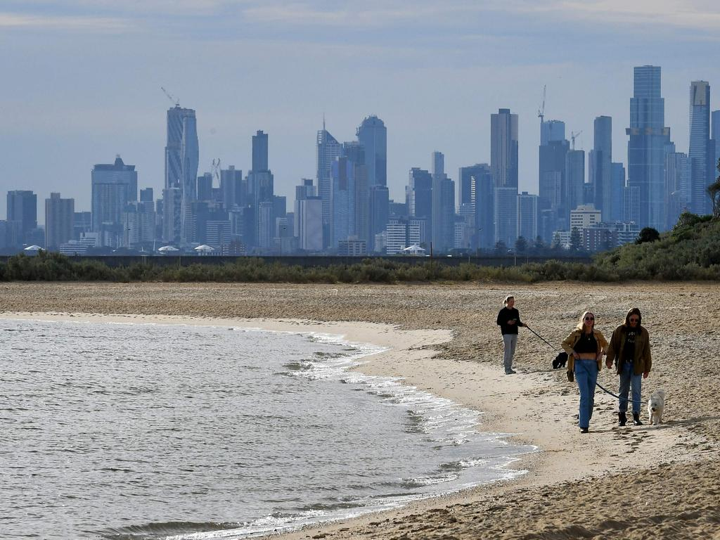 People enjoy a mid-winter walk on Brighton Beach in Melbourne yesterday as the city's latest Covid-19 outbreak recedes while Sydney battles a fresh cluster. Picture: William West AFP)