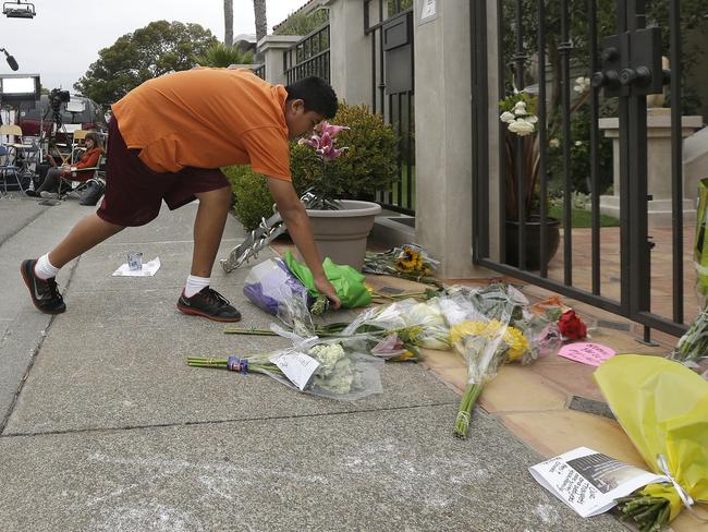 Brandon Antonio, 13, of San Rafael, leaves flowers outside of the home of Robin Williams.