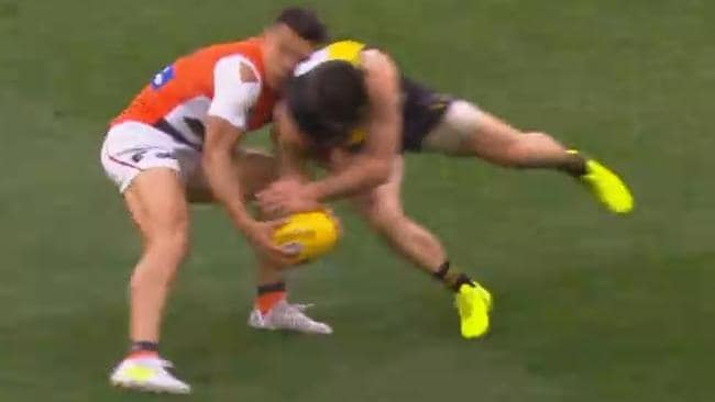 Richmond skipper Trent Cotchin collects GWS Giant Dylan Shiel.