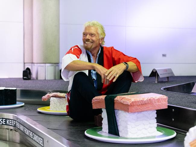 Sir Richard Branson takes a ride on a baggage carousel at Brisbane Airport. Picture: Virgin Australia