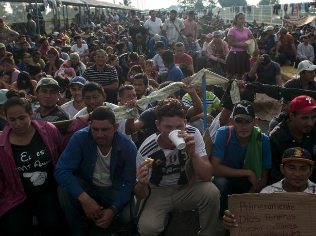 Honduras migrants wait to be attended by Mexican migration authorities on a bridge connecting Guatemala and Mexico. Picture: AP Photo/Oliver de Ros