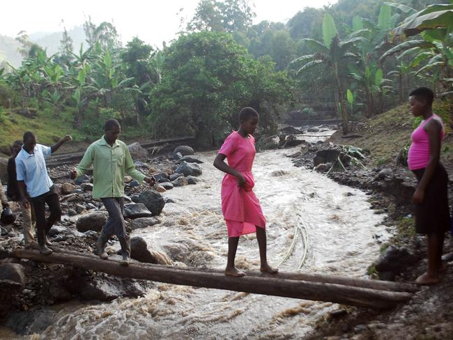 Residents cross a swollen river after the disaster. Picture: AP Photo/Ronald Kabuubi