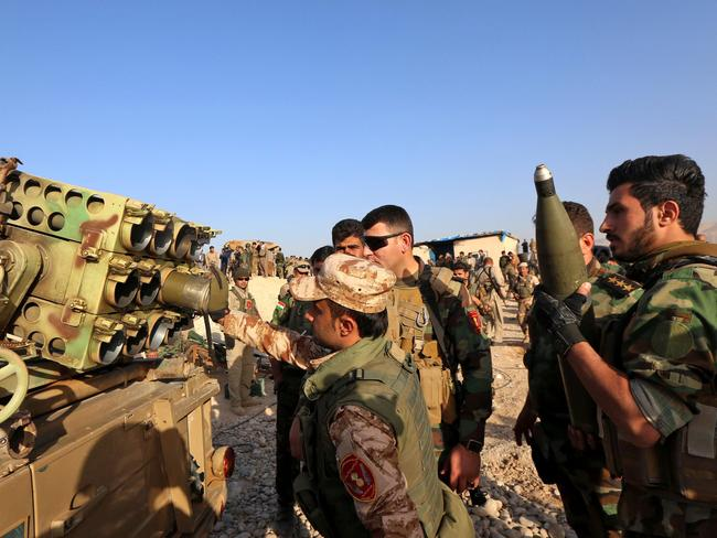 Iraqi Kurdish Peshmerga fighters prepare to fire a multiple rocket launcher as they hold a position in Sheikh Ali village near the town of Bashiqa. Picture: Safin Hamed/AFP