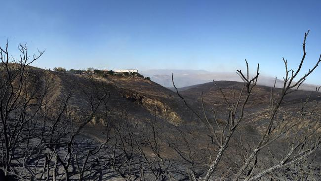 Burned hillsides surround the Ronald Reagan Presidential Library on Wednesday, Oct. 30, 2019, in Simi Valley, Calif. A wind-whipped outbreak of wildfires outside Los Angeles threatened thousands of homes and horse ranches, forced the smoky evacuation of elderly patients in wheelchairs and narrowly bypassed the library, protected in part by a buffer zone chewed by goats. (Dean Musgrove/The Orange County Register/SCNG via AP)