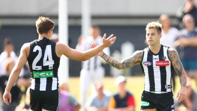 Jamie Elliott of the Magpies is congratulated by Josh Thomas of the Magpies after kicking a goal during the AFL Practice Match between Collingwood and Melbourne at Olympic Park Oval.