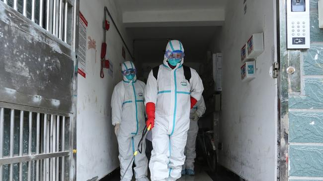 Staff members wearing protective clothing, disinfecting a residential area in Ruichang, part of Jiujiang in China's central Jiangxi province next to Hubei province. Picture: STR/AFP