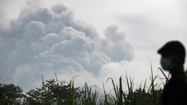 Volcanic ash from a major eruption in Indonesia shrouded a large swath of the country's most densely populated island on Friday, closed three international airports and sent thousands fleeing. Picture: AP Photo/Trisnadi