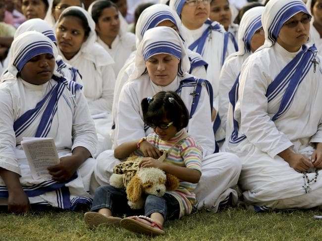 An orphan girl plays with a toy as she joins the nuns of Missionaries of Charity, the order founded by Saint Teresa, during a mass in Kolkata, India. Picture: AP