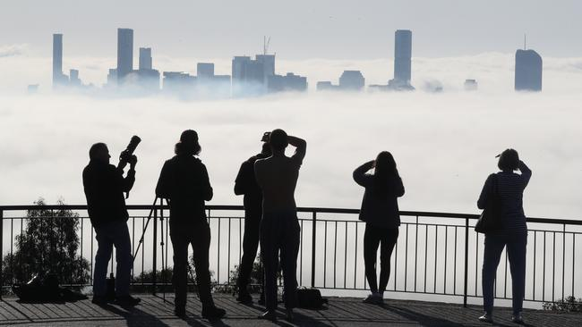 Brisbane was bathed in winter fog this morning with onlookers surveying the city from Mt Cootha. Picture: Annette Dew