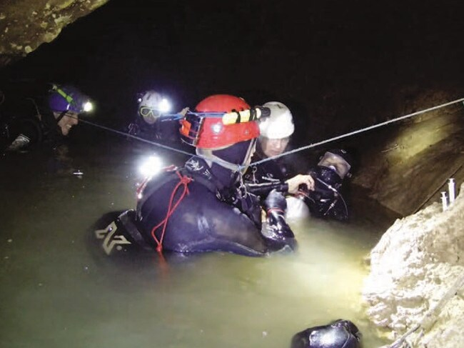 One of the Thai cave boys with his full mask on supported by members of the cave diving team including Chris Jewell, Rick Stanton and John Volanthen. Picture: Richard Harris.