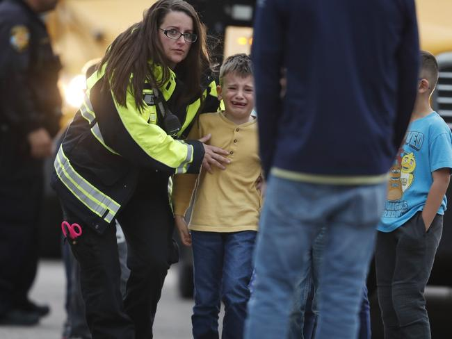 Officials guide students off a bus and into a recreation centre where they were reunited with their parents. Picture: David Zalubowski/AP