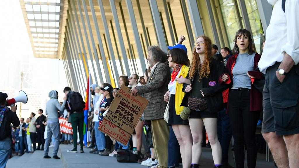 Activists link arms to block an entrance to the Melbourne Exhibition and Convention Center. Picture: AAP Image / James Ross