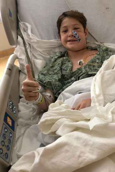 Xavier Cunningham, 10, gives the thumbs up from his hospital bed after he was impaled in the head by a meat skewer in a freak accident. Picture: Courtesy Shannon Miller via AFPSource:AFP