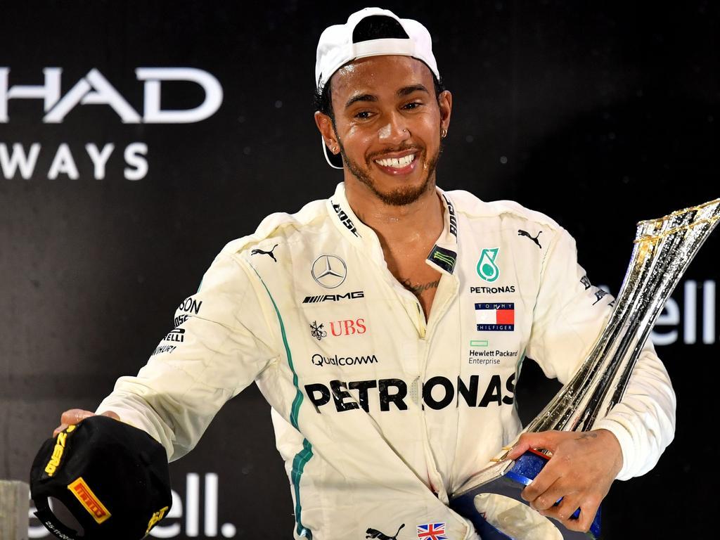 TOPSHOT - Mercedes' British driver Lewis Hamilton celebrates on the podium after winning the Abu Dhabi Formula One Grand Prix at the Yas Marina circuit on November 25, 2018, in Abu Dhabi. (Photo by Andrej ISAKOVIC / AFP)