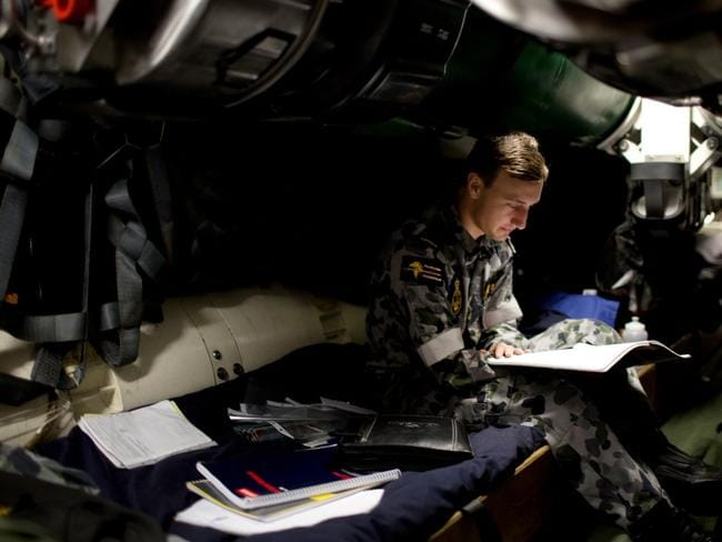 Seaman in training Callum Donald studies his part three submarine sea qualification taskbook inside the weapons stowage compartment of one of the Navy's existing submarines. Picture: Royal Australian Navy