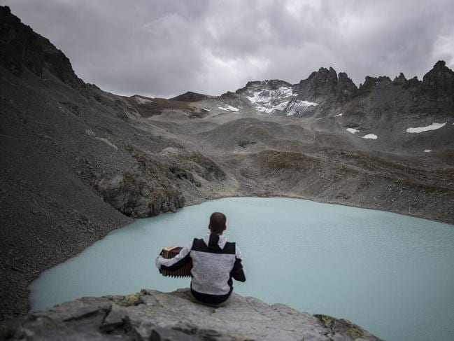 "A hiker with a view of Wildlake and the Pizol glacier on the sideline of a commemoration for the ""dying"" glacier of Pizol mountain. Picture: AP"