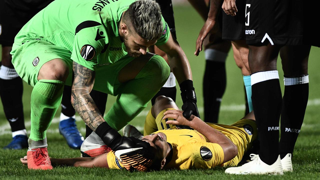 Pedro lies on the ground as PAOK's goalkeeper checks on him.