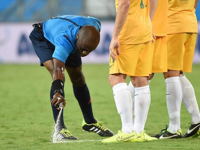 Ivorian referee Noumandiez Doue sprays a free kick marker on the pitch during a Group B football match between Chile and Australia.