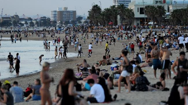 Crowds gather at St Kilda Beach to escape the heat and to watch the sunset.