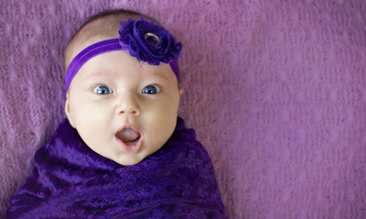 Happy and surprised expression on a 2 month old baby girl, with copy space. Purple background.