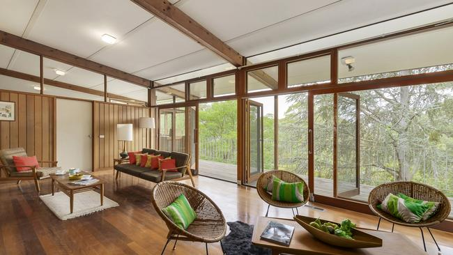 Designed by renowned local architect John Hipwell, the home offers panoramic treetop views.