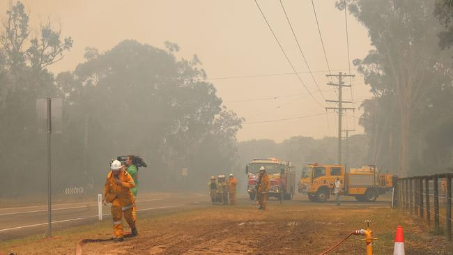 Firefighters are seen near fires at Lake Cooroibah Road and Jirrimah Crescent in Cooroibah in Noosa Shire, Queensland. Picture: AAP Image/Rob Maccoll