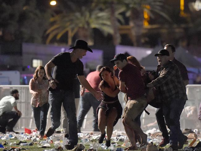 People carry a person at the Route 91 Harvest country music festival after a mass shooting carried out from a hotel balcony. Picture: AFP PHOTO / GETTY IMAGES NORTH AMERICA / David Becker