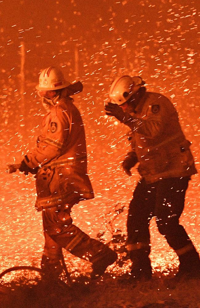 Firefighters struggle as strong winds blow embers into their faces near Nowra, two hours south of Sydney. Picture: Saeed Khan/AFP