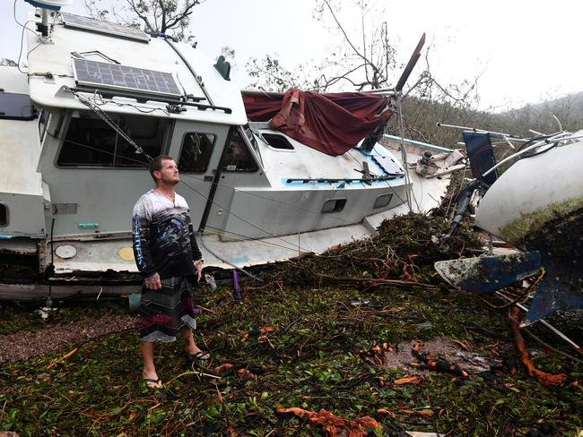 Bradley Mitchell inspects the damage to his uncle's boat after it smashed against the bank at Shute Harbour near Airlie Beach. Picture: AAP Image/Dan Peled