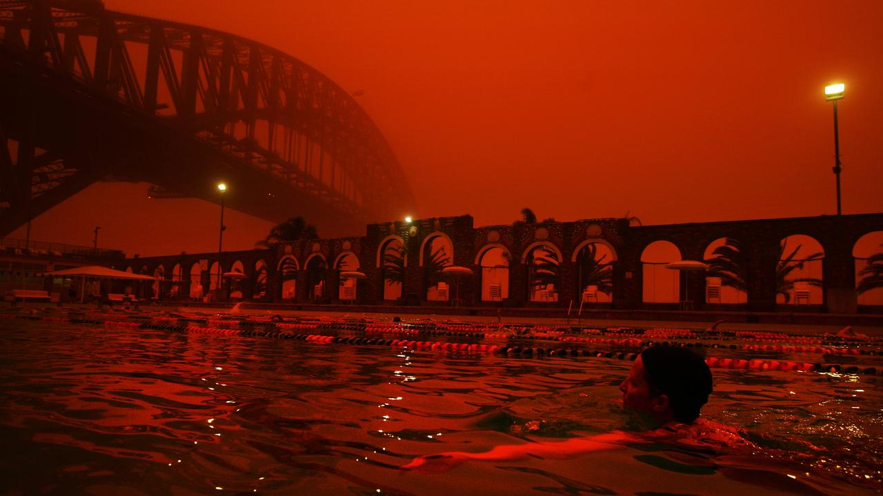 Swimmers take an early morning swim at North Sydney pool as a red haze blankets Sydney from a dust storm created by overnight inland winds.
