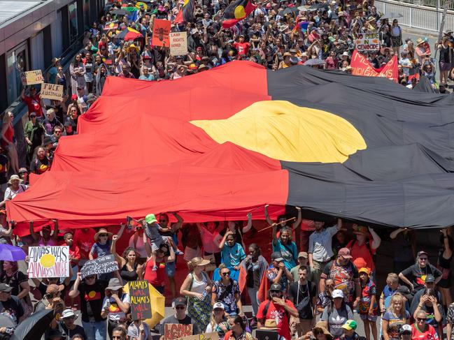Invasion Day protesters holding a large flag as they march in Brisbane. Picture: Glenn Hunt