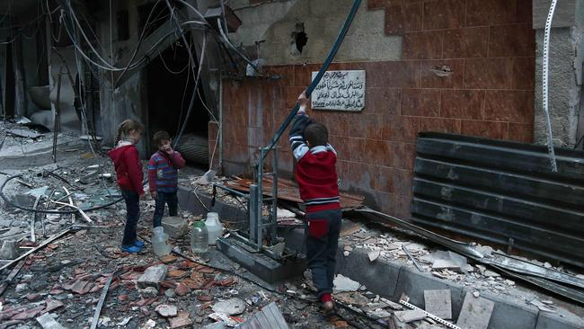 Syrian children fill plastic containers at a water pump in the ruins of Arbin in the rebel-held enclave of Eastern Ghouta. Picture: AFP/Abdulmonam Eassa