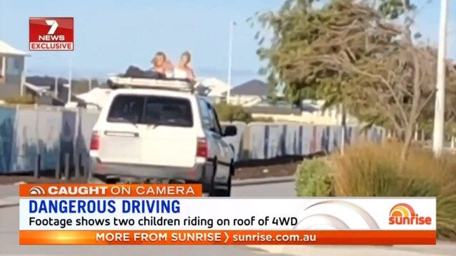 Two girls ride on top of 4WD (Sunrise)
